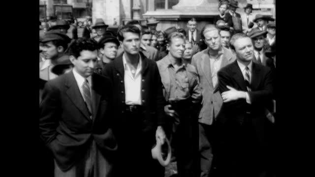 / flashback dramatization to 1932 berlin about the rise of nazism / regular men standing around listening to propaganda / narrator explains the men... - 1945 stock-videos und b-roll-filmmaterial
