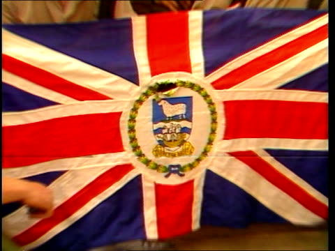 vídeos de stock e filmes b-roll de flashback itn lib port stanley cs union jack pull back to group of royal marines posing with it itn 21secs tx'd17682/nat archive tape 20072 3237 to... - ilhas malvinas