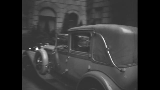 Flashbulbs pop as exiled Queen Victoria Eugenie of Spain approaches gets into car upon arrival in New York / montage Queen's car arrives at Columbia...