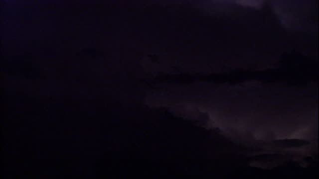 Flashes of lightning illuminate a stormy sky. Available in HD.