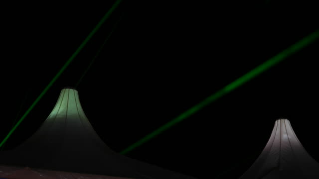 flashing laser display at a music festival, overhead on top of the festival tents - マルチメディア点の映像素材/bロール