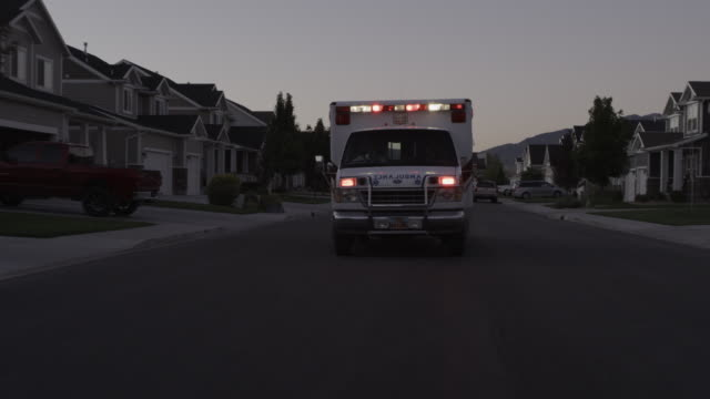 vídeos de stock, filmes e b-roll de flashing lights of ambulance driving on neighborhood street / lehi, utah, united states - ambulância