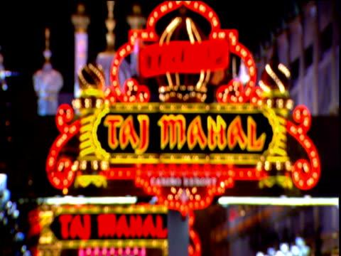 vídeos de stock, filmes e b-roll de flashing neon sign for trump taj mahal casino pull out of focus - atlantic city