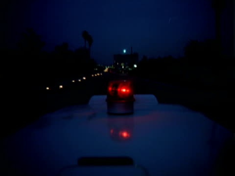 MONTAGE CU Flashing siren on top of ambulance speeding through heavy traffic and a Schaefers Ambulance sign and ambulance racing through street at night / Los Angeles, California, United States