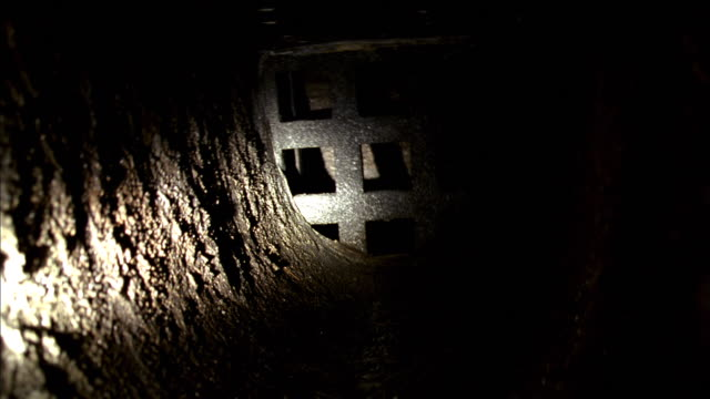 pov flashlight beam playing over metal grate covering exit from tunnel - electric torch stock videos & royalty-free footage