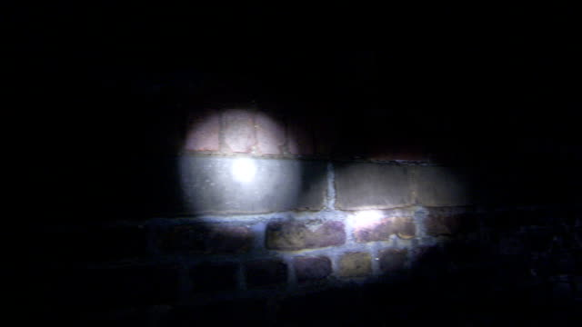 flashlights shine on brick walls inside an underground sewer in london. available in hd. - electric torch stock videos & royalty-free footage