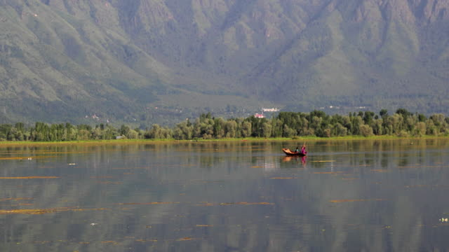 A flat bottomed rowboat in Dal Lake in Kashmir Valley with the might Zabarwan mountain range of the Himalayas in the background