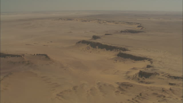 a flat desert stretches toward a distant horizon. - egypt stock videos & royalty-free footage