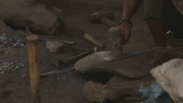 a flat metal object is shaped using a hammer at a workshop in sierra leone. - steamroller stock videos and b-roll footage