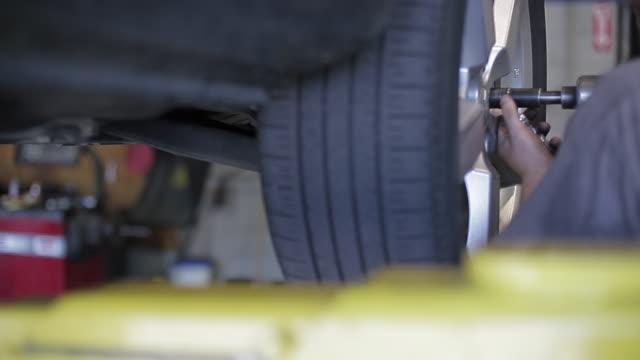 flat tire repair and car maintenance at garage - 自動車部品点の映像素材/bロール