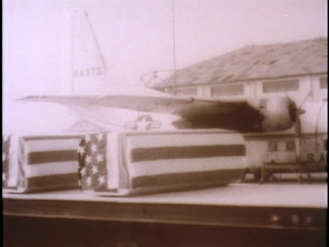 a flatbed trailer truck carries american flagdraped coffins past mourning us sailors - 棺点の映像素材/bロール