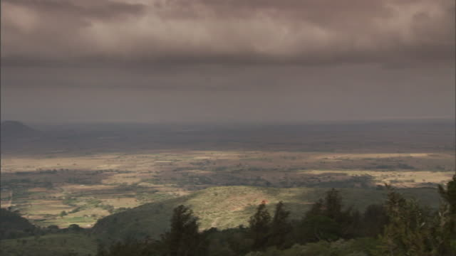 flat-bottomed clouds hang above a dry valley. - east africa stock videos & royalty-free footage