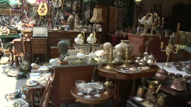 POV A flea market with various antiques and curiosities on display and a customer browsing / Greece