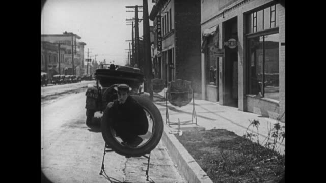 1921 fleeing police, worried man (buster keaton) accidentally hides in a tire sign rather than a tire - 1921 stock videos & royalty-free footage