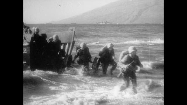 fleet just off shore including landing crafts w/ us marines moving / vs heavy bombing across iwo jima landing crafts w/ us marines landing on shore... - schlacht um iwojima stock-videos und b-roll-filmmaterial
