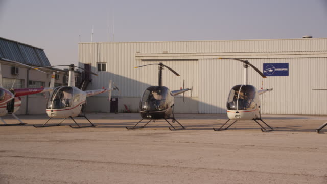 pan fleet of helicopters outside hangar, red r3d 4k - medium group of objects stock videos & royalty-free footage