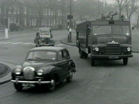 A fleet of London Auxiliary Fire Service vehicles travel along London streets
