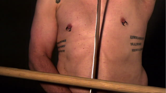 flesh on a man's naked, pierced and tattooed torso ripples as a stick hits a sword. - torso stock videos & royalty-free footage
