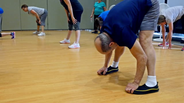 Flexible senior man stretches in exercise class