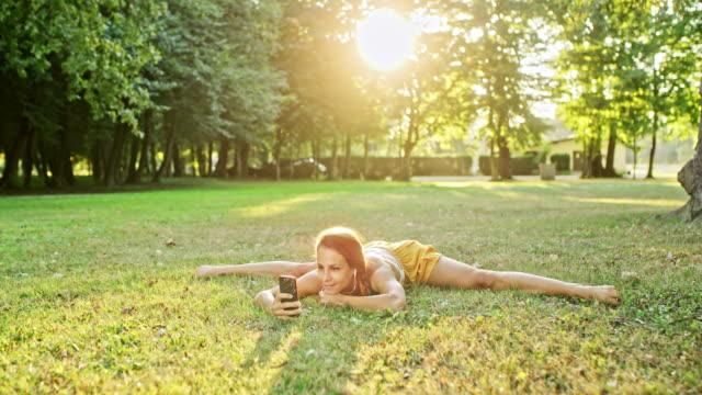 stockvideo's en b-roll-footage met ms flexibele jonge vrouw het beoefenen van splitsingen, met behulp van slimme telefoon in grass in sunnypark - benen gespreid