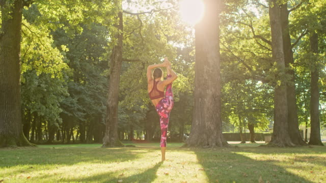 ms flexible young woman practicing standing splits in sunny park - leggings stock videos & royalty-free footage