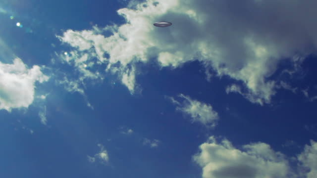 a ufo flies through a clouded blue sky. - ufo点の映像素材/bロール