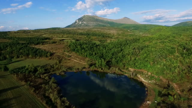 vídeos de stock, filmes e b-roll de voo sobre o lago de montanha - viaduto entroncamento