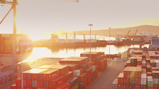 vídeos de stock e filmes b-roll de flight across intermodal shipping yard at sunset - docas