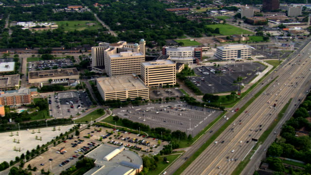 flight along freeway past memorial hermann hospital complex in houston. shot in 2007. - medical building stock videos & royalty-free footage