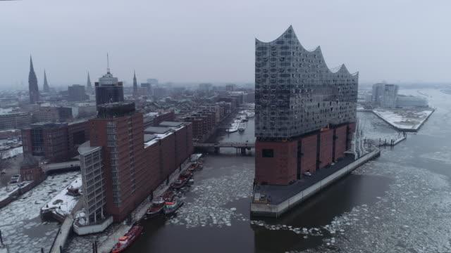 flight around elbphilharmonie with cloudy winter weather - hamburg stock-videos und b-roll-filmmaterial