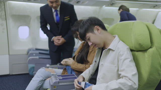 flight attendant advising the couple for fastening the seat belt - passenger seat stock videos & royalty-free footage