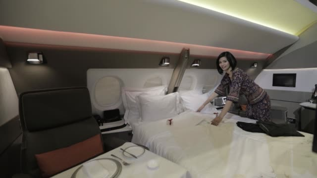 a flight attendant arranges a bed in two adjoining mockup suites designed by pierrejean design studio during the unveiling of the new cabins for the... - beifahrersitz oder rücksitz stock-videos und b-roll-filmmaterial