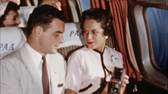 A flight attendant assists airplane passengers as they settle in to enjoy their flight.