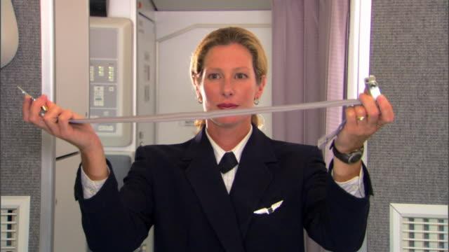 stockvideo's en b-roll-footage met a flight attendant demonstrates proper usage of a seatbelt to unseen passengers before an airline flight. - veiligheidsgordel