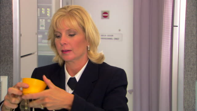 a flight attendant demonstrates proper usage of the oxygen masks in case of an emergency on an airline flight. - crew stock videos & royalty-free footage