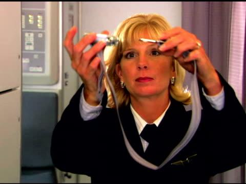 vídeos de stock, filmes e b-roll de flight attendant demonstrating safety - tripulação