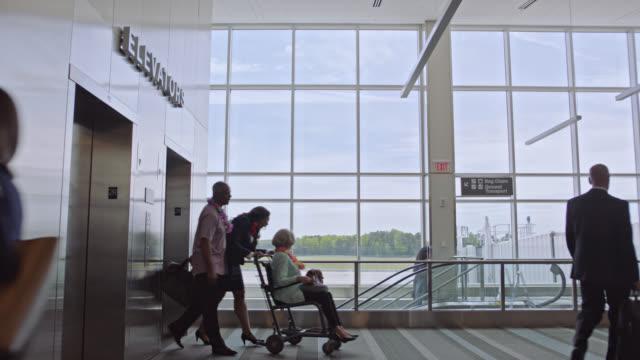 flight attendant exists elevator pushing elderly woman in wheelchair with companion walking beside. - rullstol bildbanksvideor och videomaterial från bakom kulisserna