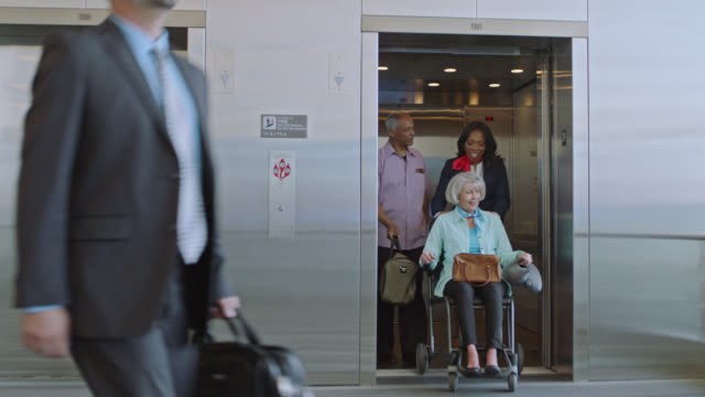 flight attendant exists elevator with elderly couple, the wife in a wheelchair. - disability stock videos & royalty-free footage