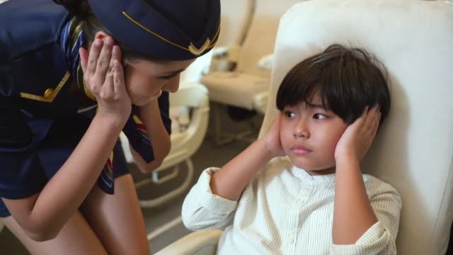 vidéos et rushes de l'agent de bord donne des conseils au garçon pleurant pour couvrir ses oreilles en vol - dedans