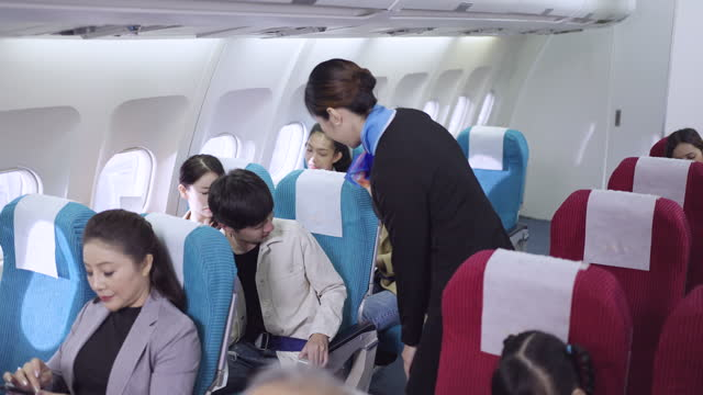 flight attendant guide the young male passenger in flight - passenger seat stock videos & royalty-free footage