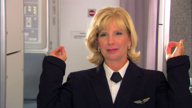 A flight attendant points to the emergency exit locations in the cabin of the airplane.