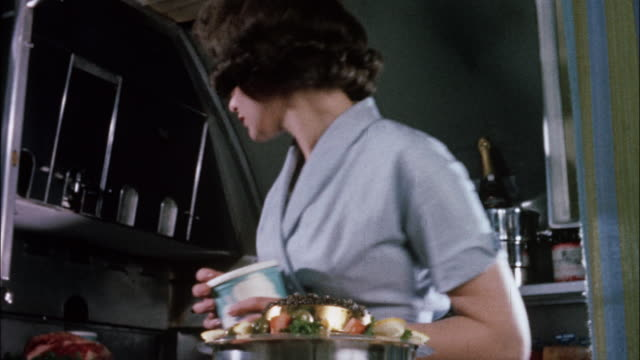 a flight attendant prepares elegant food on an upscale airliner. - galeere stock-videos und b-roll-filmmaterial