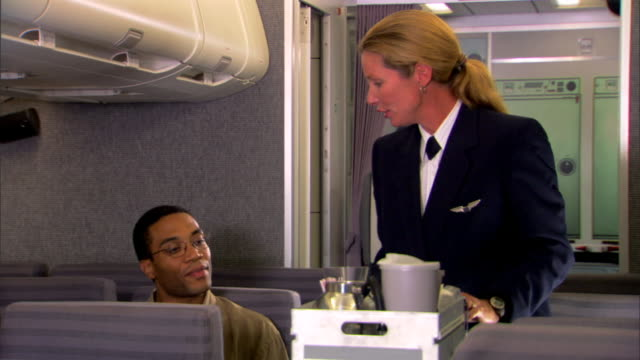 a flight attendant pushes a cart up the aisle of an airplane to serve snacks and drinks to a passenger. - crew stock videos & royalty-free footage