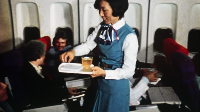 A flight attendant serves drinks to passengers and another flight attendant aids a first class passenger by stowing his garment bag and briefcase.
