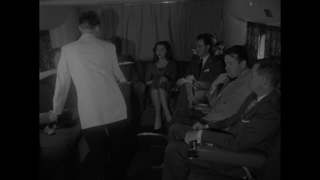 flight attendant serving dinner on tray to woman passenger woman passenger sitting next to her looks on / model comes down steps into lounge and... - serving tray stock videos and b-roll footage