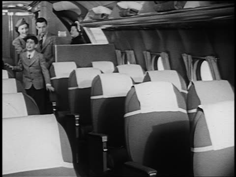B/W 1951 flight attendant talking to two boys entering airliner + sitting in seats / others follow