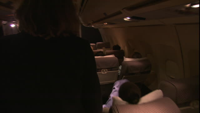 a flight attendant walks down an airplane aisle. - crew stock videos & royalty-free footage