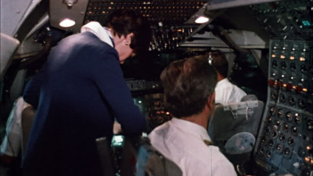 Flight attendants prepare drinks and serve the passengers and pilots during a Pan Am flight.