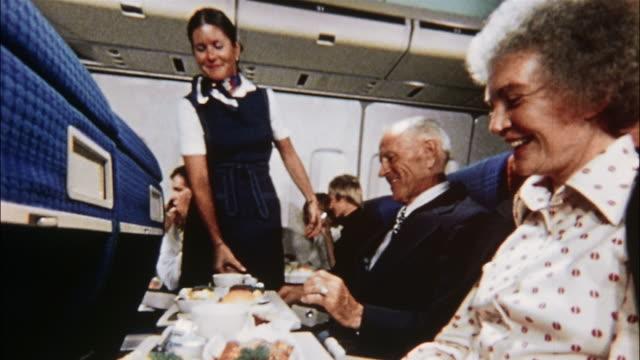 flight attendants serve food and coffee to a senior couple on an airplane. - dienstleistungsberuf stock-videos und b-roll-filmmaterial