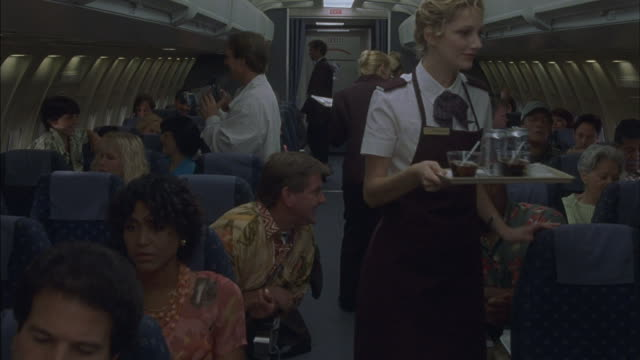 Flight attendants serve passengers on an airplane.